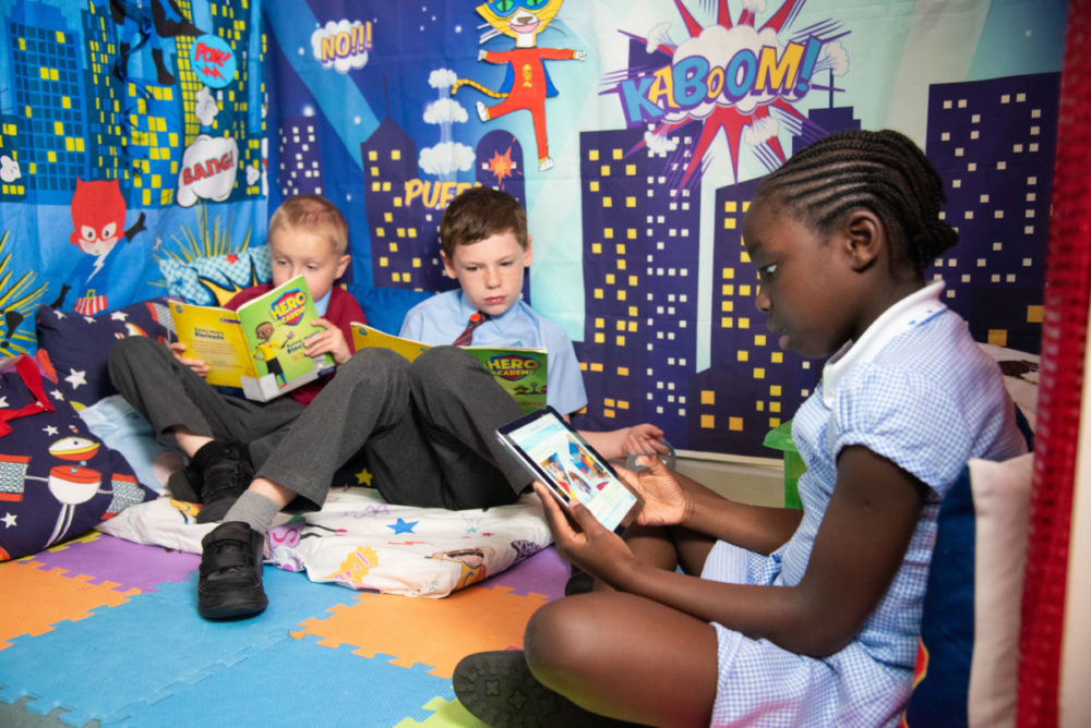 Primary children reading books and a tablet in a reading corner